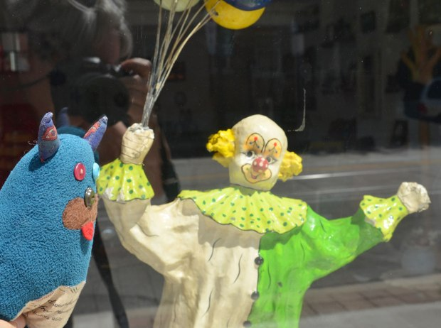 Edgar is looking into a store window.  A figurine of a clown holding a bunch of balloons is looking back at Edgar.