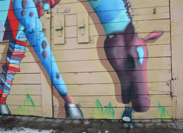 Edgar the little blue monster is sitting on the ground by a mural of a multicoloured horse. It looks like he's right beside the horse's mouth. The horse is standing on four legs but has it's head bent down towards the ground.
