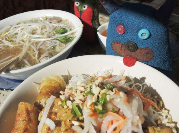 Edgar the blue monster and Flora the little green thing are each sitting beside a very large bowl of pho in a restaurant.