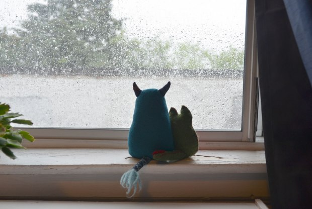 Edgar and Flora are sitting on the window sill looking out at the rain on a grey and wet day