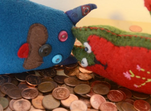 Edgar the little blue monster and Flora his little green friend are lying head to head on a pile of Canadian pennies