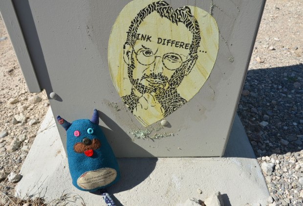 Edgar is sitting beside a grey metal box on a sidewalk. On the box is a wheatpaste picture of a man with beard and glasses with the words think different written on it.