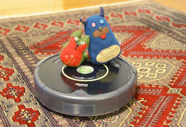 Edgar the little blue monster and his friend Flora are sitting together on a roomba, a robotic vacuum cleaner, on a carpet on the floor.