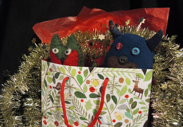 Edgar the little blue monster and his friend Flora are all wrapped up in red tissue paper and a Christmas gift bag and decorated with a shiny gold garland.