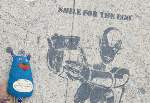 Edgar is lying on the sidewalk beside a stencil of a robot holding a smartphone and taking a selfie. The words with the stencil are smile for the ego