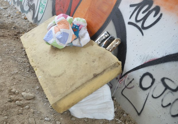 Edgar is wrapped up in a small quilt that's on a foam mattress that is leaning against a bridge supprt outside. Some empty spray paint cans are beside him. There is an old pillow on the ground.