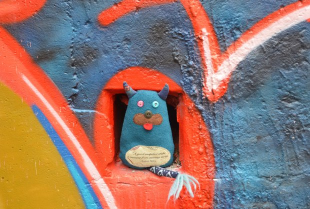 Edgar is standing in a small square hole in a wall. He just fits in it. The hole is in the middle of some red, blue and yellow graffiti.