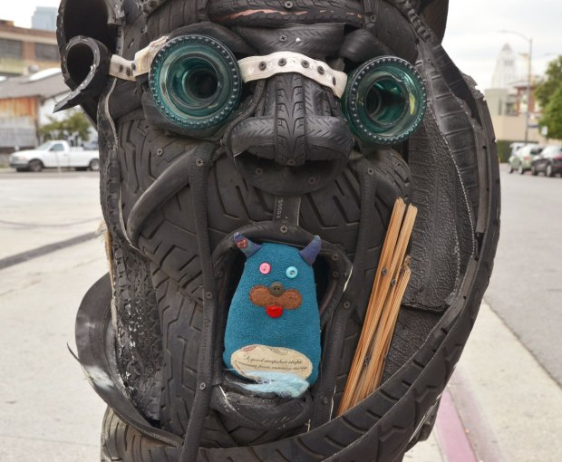 a telephone pole has been decorated with tires that have been made into faces. Edgar is sitting in the mouth of one of these faces