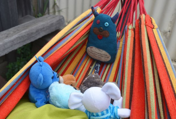 Edgar is sitting on a striped hammock, he is looking at 5 other little stuffed animals who are also sitting on the hammock, listening to Edgar