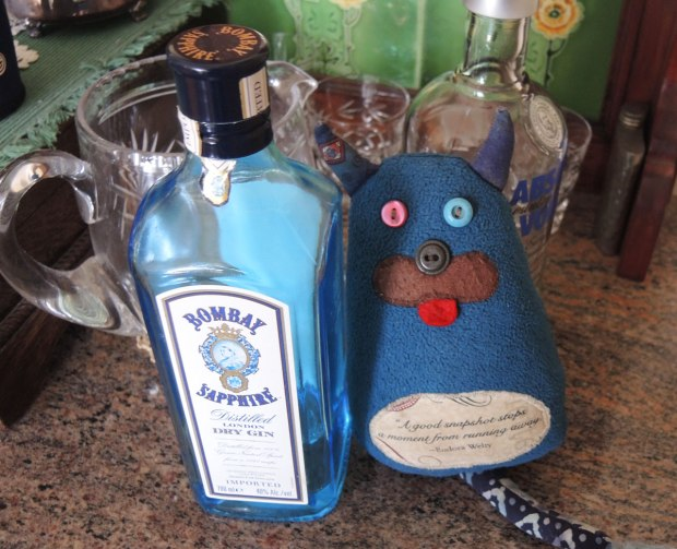 Edgar the little blue monster is standing beside a bottle of Bombay Sapphire gin