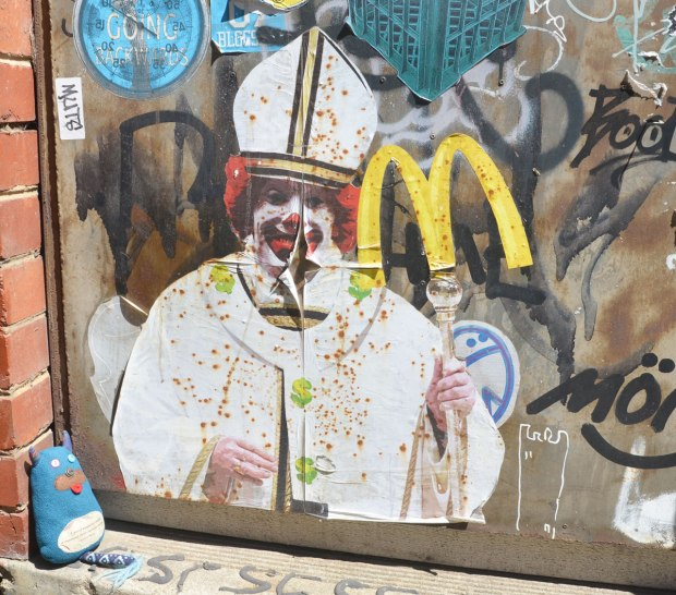 graffiti paste ups on a door in an alley, the pope with the face of Ronald McDonald, plus the yellow M for McDonalds on top of the pope's staff. Edgar is sitting in front it, looking at the pope