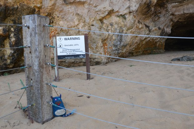 Edgar is sitting on the sand, beside a concrete post, and just behind a wire fence. Behind him is a sign that says warning, unstable cliffs, and behind the sign are the cliffs.