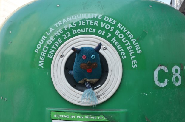 Edgar is sticking his head out a large green recycling bin in Paris