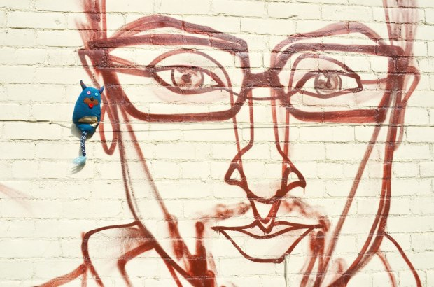 edgar is standing beside the ear of a face painted on a wall by street artis anser - a man's face, wearing glasses