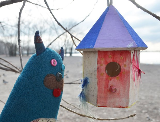 Edgar is looking at a little bird house that someone has hung from a tree branch on Cherry Beach. It has a red front and a purple roof. The beach and Lake Ontario is in the background.