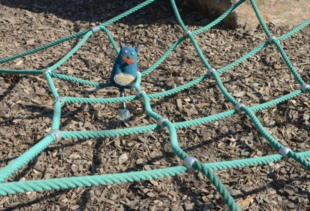 Edgar is standing on a set of blue ropes joined together in a grid to make a small climbing rope frame in a playground. There are wood chips under the ropes. The ropes are only a couple of inches off the ground.