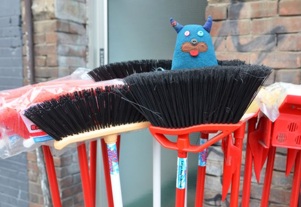 brooms for sale outside a store.  They are brush end up.  Edgar is sitting on one of them.