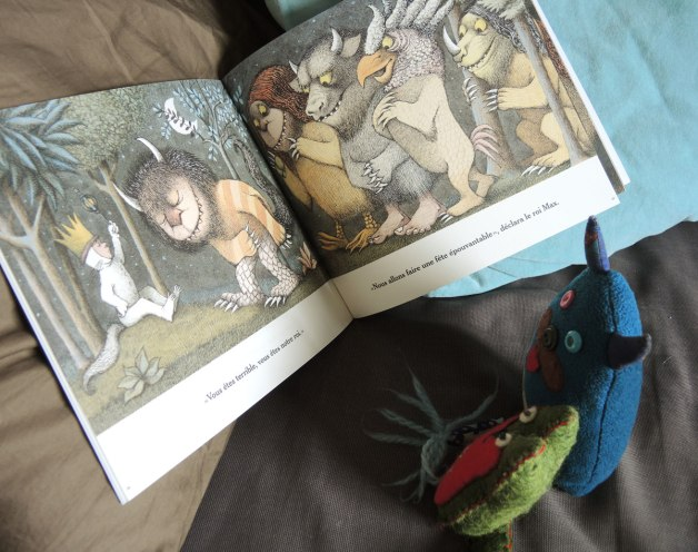 Edgar the little blue monster and his friend Flora are reading a book, Max and the Wild Things by Maurice Sendak, but in french.
