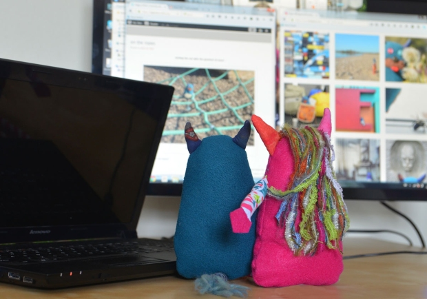 Edgar the little blue monster, and Miss Nothing, the little pink monster sit in front of a computer monitor looking at Edgar's pictures on his blog and on his instagram page.