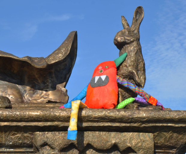 Bo, the rainbow coloured stuffed monster is sitting on a statue beside a small bronze rabbit.