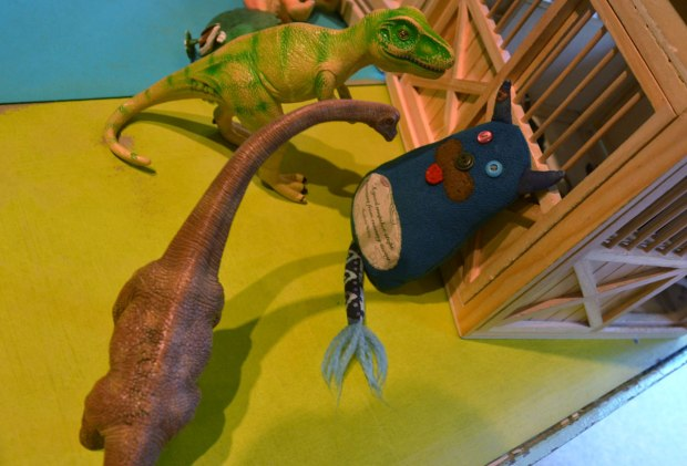 Edgar is standing on a table, his back against a toy wooden stable and barn. Two large plastic dinosaurs are face to face with him. A brown brontosaurus and a green and beige one