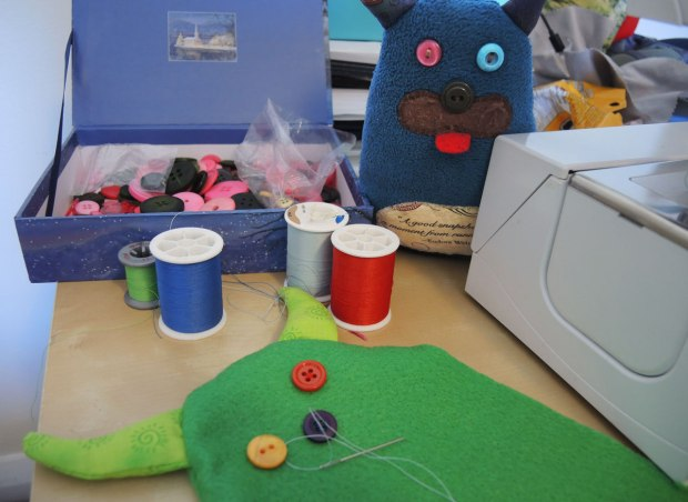 Edgar is standing by a sewing machine, a box of buttons and 4 spools of thread, green, dark blue, light blue and red thread. In the foreground is the beginnings of a new green monster. One red eye has already been sewn on. A yellow eye and a blue nose are in place but haven't been sewn on yet.