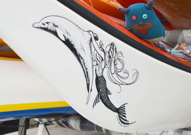 Edgar is lying on a kayak so he can get a better view of the mermaid and dolphin that are painted on the side at the end of the kayak