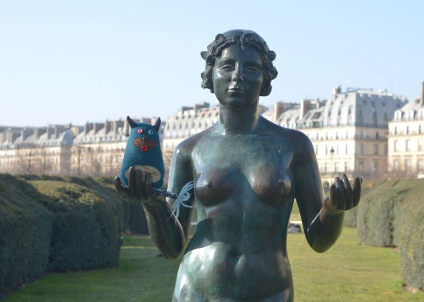 edgar is standing in the open hand of a statue of a naked women in a park in Paris
