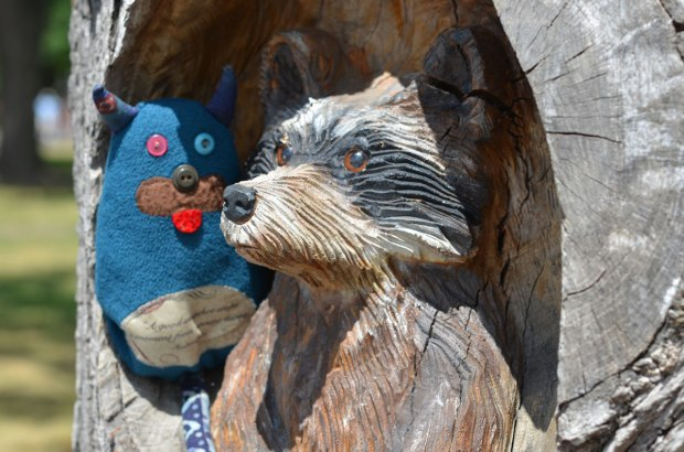 Edgar is sitting close to a wood sculpture of a raccoon head. The raccoon is staring into the distance