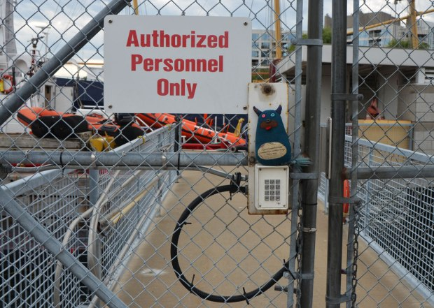 "Edgar the little blue monster is standing on top of a keypad that unlocks a chainlink gate. A large sign that says ""authorized personnel only"" is beside his head. Boats and docks are behind the fence and gate."