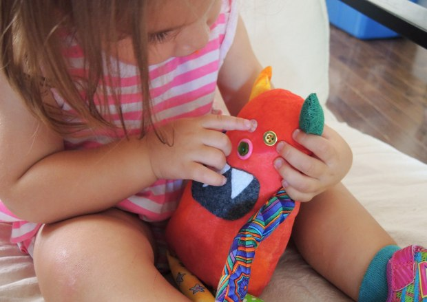 Bo, the rainbow coloured stuffed monster is sitting in a little girl's lap, she is poking at his button eyes