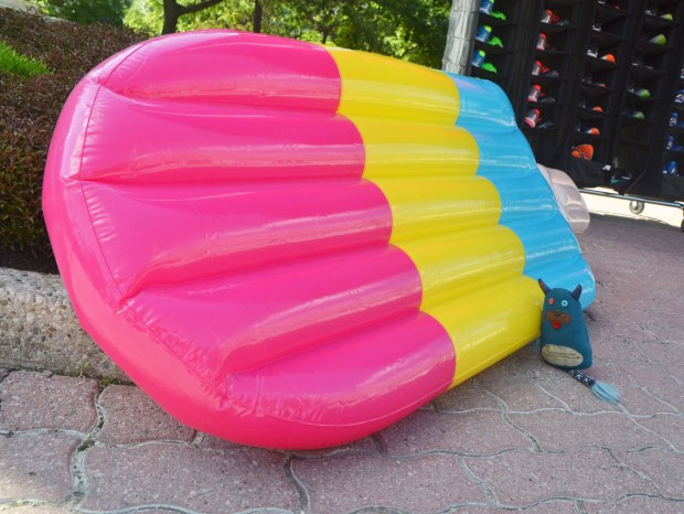 Edgar is standing on the sidewalk beside a giant inflatable popsicle in pink, yellow and blue