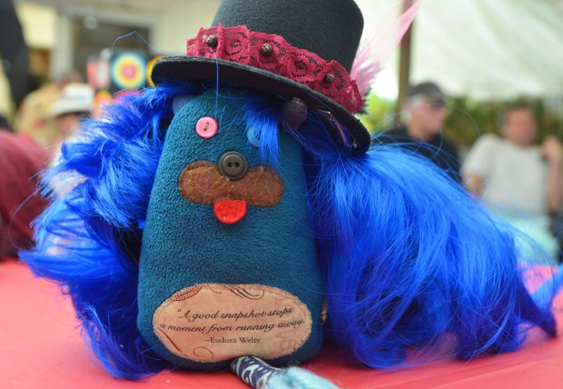 edgar is standing on a table with a large blue wig on as well as a black top hat with pink lace on it