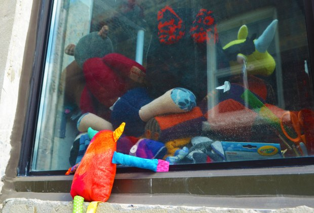 Bo, the rainbow coloured monster is looking into a window where there are some stuffed animals inside.