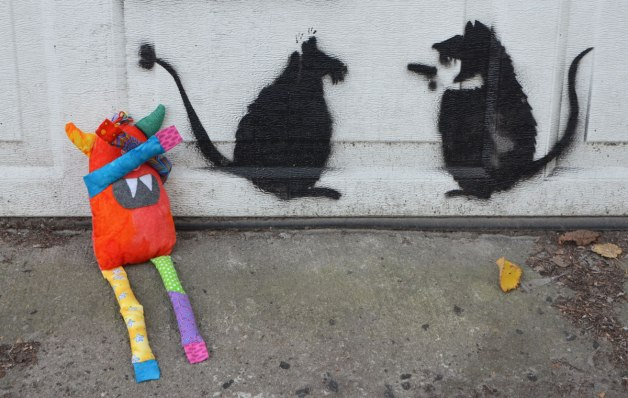 Bo, the stuffed rainbow coloured monster is sitting beside a white garage door with his arms covering his eyes. On the garage door is a stencil of two rats, One is holding a gun and pointing it at the other rat.