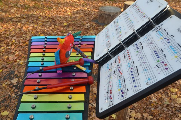 bo, the little rainbow coloured monster is sitting on a large xylophone with bright coloured keys. Sheet music is in front of him. The xylophone is outdoors and there are lots of autumn leaves on the ground around him.
