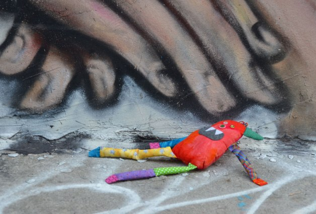 Bo the little rainbow coloured stuffed monster is lying on the concrete sidewalk at the edge of a building. On the building is a street art painting of two hands with their fingers pointed downwards. Bo is lying under the fingers.