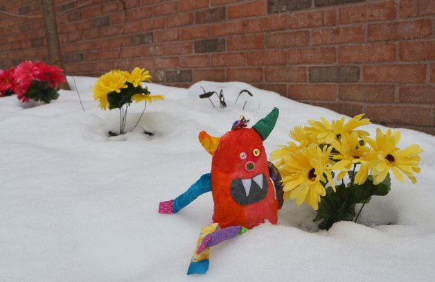 bo the stuffed rainbow coloured monster is sitting in the snow beside a bunch of bright yellow plastic flowers. Other bunches of cloers in reds and purples are also in the photo