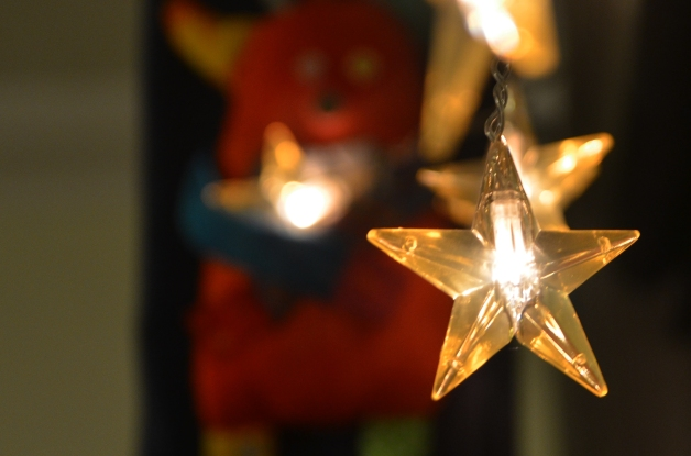 Bo is holding a small Christmas light in the shape of a star, he is behind a row of other identical stars, in the semi darkness