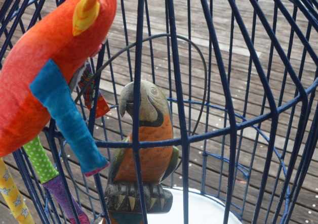 Bo, the stuffed rainbow coloured monster is looking into a metal cage where there is a wooden parrot on a perch.