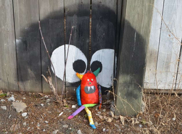 bo, the little rainbow monster is sitting in the dirt on the ground, sitting against a wood fence, a large black circle with two big eyes has been painted on the fence and Bo is sitting between the eyes