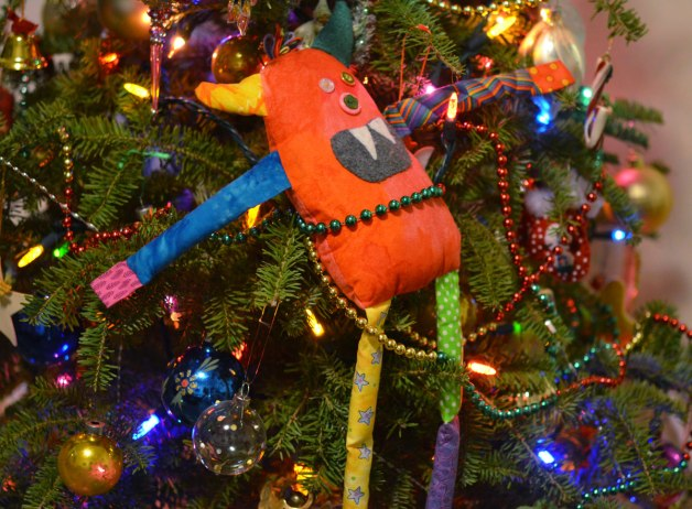 bo, the rainbow coloured stuffed monster is tied to the Christmas tree with sparking green, gold, and red beaded cord